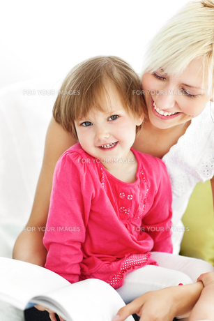 Smiling mother reading a book with childrenの素材 [FYI00483078]
