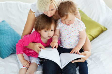 Cute mother reading a book with childrenの写真素材 [FYI00483079]