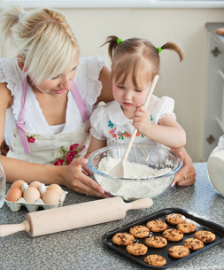 Smiling woman baking cookies with her daughtersの写真素材 [FYI00483106]
