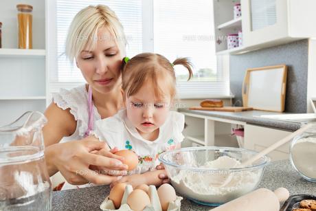 Focused woman baking cookies with her daughterの写真素材 [FYI00483124]