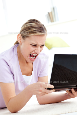 Furious young woman screaming at her laptopの写真素材 [FYI00483154]