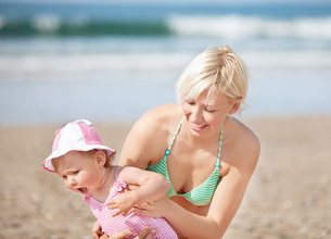 Smiling mother at the beach with her daughterの写真素材 [FYI00483159]