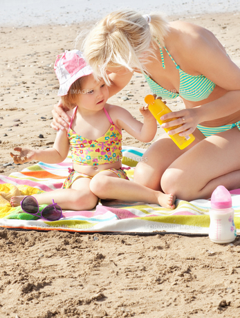 Attentive mother at the beach with her daughterの写真素材 [FYI00483160]