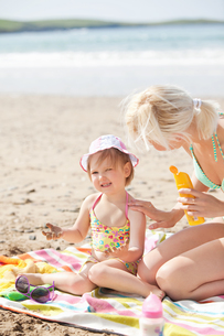 Crying little girl at the beach with her motherの写真素材 [FYI00483163]