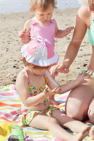 Sweet little girl using suncream at the beachの写真素材 [FYI00483164]
