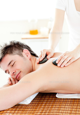 Happy young man enjoying a back massage with hot stonesの素材 [FYI00483174]