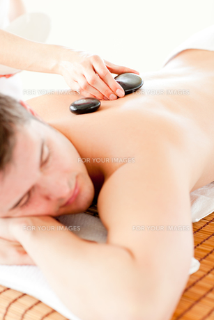 Relaxed young man receiving a back massage with hot stoneの素材 [FYI00483177]