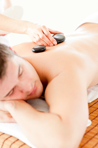 Relaxed young man receiving a back massage with hot stoneの写真素材 [FYI00483177]