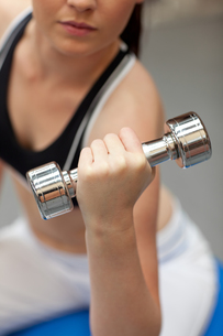 Portrait of a cute woman working out with dumbbellsの写真素材 [FYI00483182]