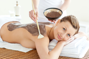 Delighted woman receiving a beauty treatment with mudの写真素材 [FYI00483190]