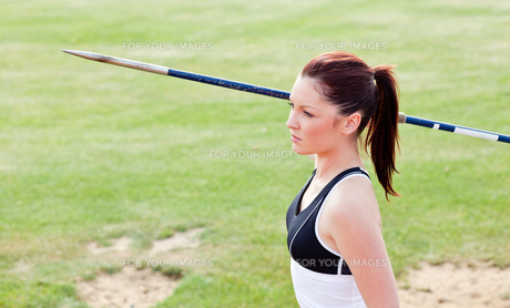 Concentrated female athlete ready to throw javelinの素材 [FYI00483197]