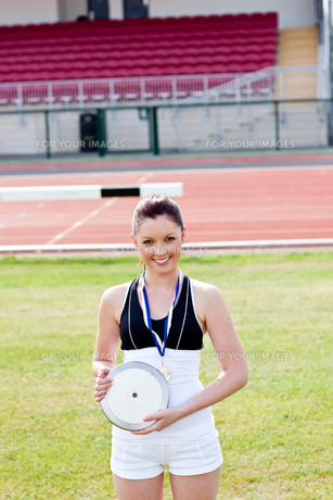Smiling female athlete with a gold medal holding a discの写真素材 [FYI00483201]