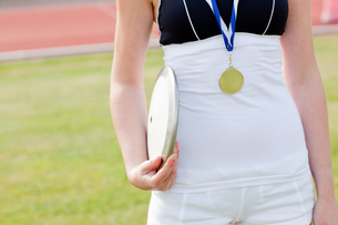Close up of a female athlete with a gold medal holding a discの写真素材 [FYI00483203]
