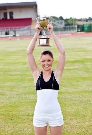Cheerful female athlete holding a trophyの写真素材 [FYI00483204]