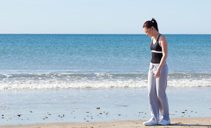 Bright woman standing on the beach and listening to musicの写真素材 [FYI00483205]