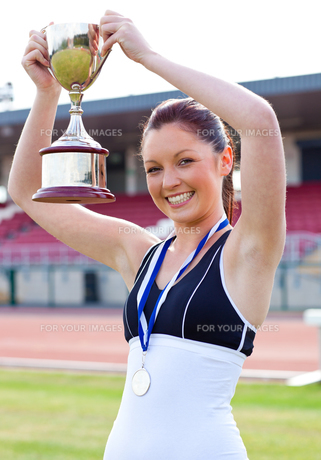 Ecstatic female athlete holding a trophee and a medalの素材 [FYI00483206]