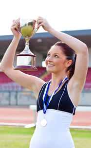 Joyful female athlete holding a trophy and a medalの素材 [FYI00483207]