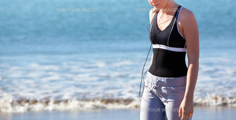 Close up of a bright woman standing on the beach and listening to musicの写真素材 [FYI00483210]