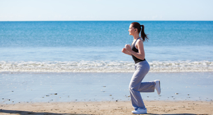 Sporty woman running on the beach and listening to musicの写真素材 [FYI00483211]