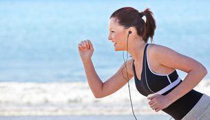 Close up of a sporty woman running on the beach and listening to musicの写真素材 [FYI00483212]