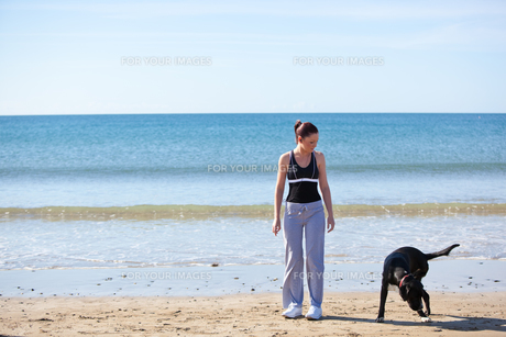Young sporty woman with a dog on the beachの素材 [FYI00483214]