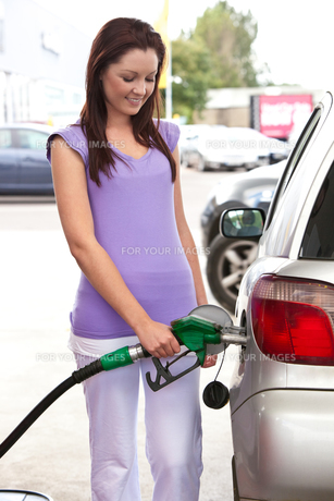 Pretty woman refueling her carの写真素材 [FYI00483220]