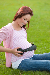 Merry pregnant woman with headphones on her bellyの写真素材 [FYI00483223]