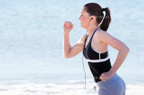 Young woman running on the beach listening musicの素材 [FYI00483235]