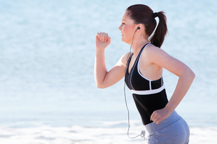 Young woman running on the beach listening musicの写真素材 [FYI00483235]