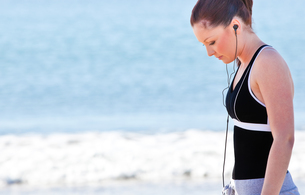 Athletic woman listening music on the beachの素材 [FYI00483237]