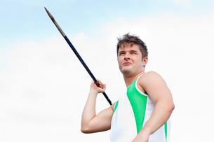Handsome male throwing a javelin outdoorsの素材 [FYI00483247]