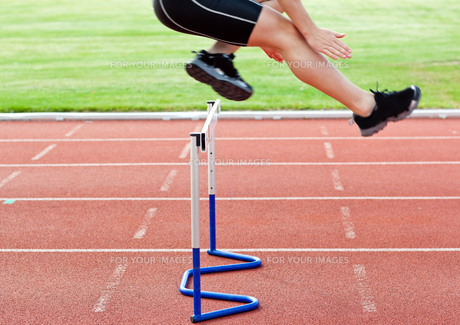 Selfassured male athlete jumping above hedge during a raceの写真素材 [FYI00483255]
