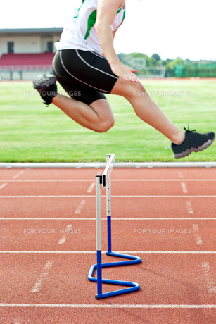 Determined male athlete jumping above hedge during a raceの写真素材 [FYI00483256]