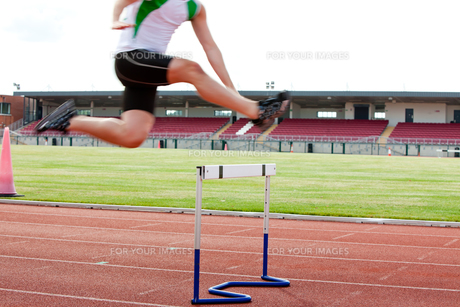 Serious male athlete jumping above hedge during a raceの写真素材 [FYI00483269]