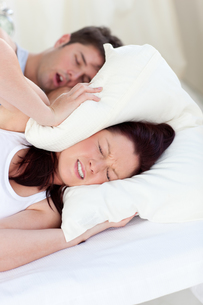 Young woman disturbed by the snores of her boyfriend in the bedroomの写真素材 [FYI00483270]