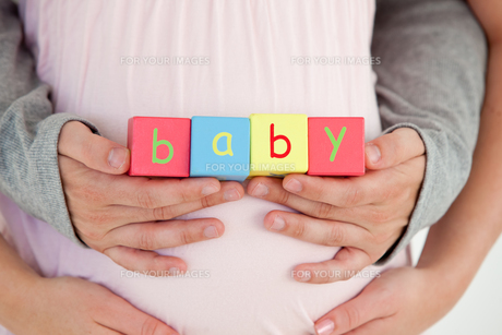 Close up of the belly of a pregnant woman and of her husband holding baby cubesの写真素材 [FYI00483275]