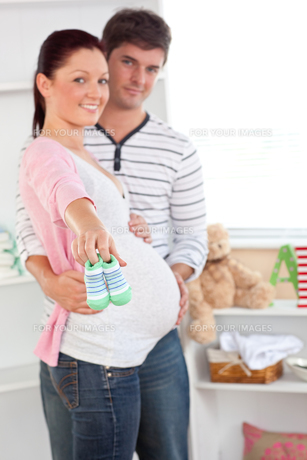 Cheerful pregnant woman holding baby shoes while husband touching her belly in the room of their futの写真素材 [FYI00483279]
