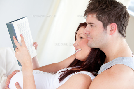 Close up of a pregnant woman and her husband reading a book on the sofaの写真素材 [FYI00483284]