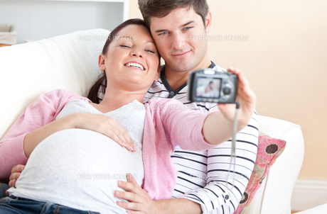 Close up of a cheerful pregnant woman and her husband taking pictures of themselves on a sofaの写真素材 [FYI00483286]