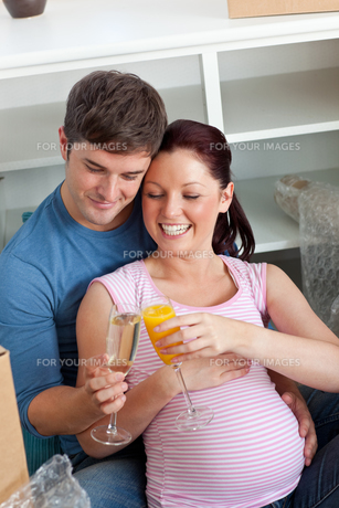 Joyful couple expecting a baby drinking and sitting on the floorの写真素材 [FYI00483291]