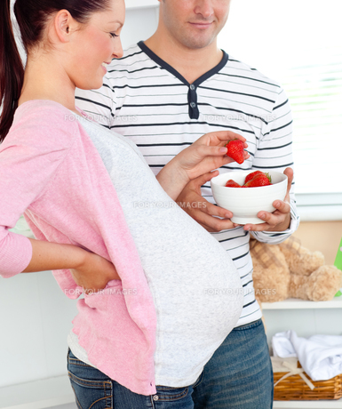 Portrait of a delighted pregnant woman eating strawberries and of her husbandの写真素材 [FYI00483292]