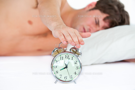 Asleep young man stopping his ringing alarm clock in the bedroomの写真素材 [FYI00483294]