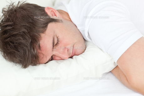 Young man sleeping in his bedの写真素材 [FYI00483296]