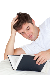 Attractive man reading a book lying on his bedの写真素材 [FYI00483297]