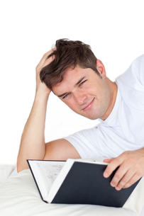Smiling man reading a book lying on his bedの写真素材 [FYI00483300]