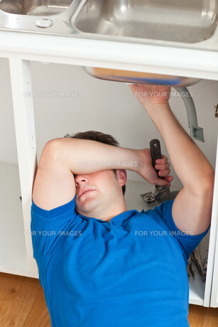 Tired man repairing his sink in the kitchenの写真素材 [FYI00483302]