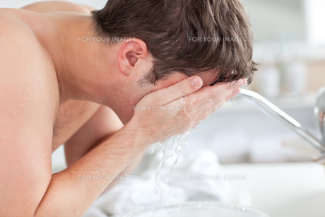 Cute man spraying water on his face after shaving in the bathroomの写真素材 [FYI00483305]