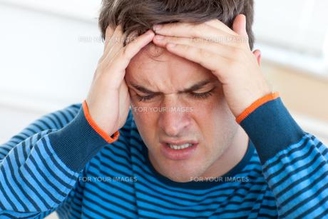 Handsome man having a headache in the livingroomの写真素材 [FYI00483307]