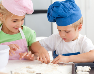 Young brother and sister kneading a dough to make cakesの写真素材 [FYI00483317]