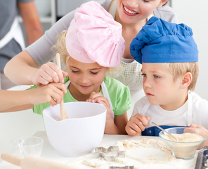 Two children and their mother stirring a preparation for cookies togetherの写真素材 [FYI00483318]
